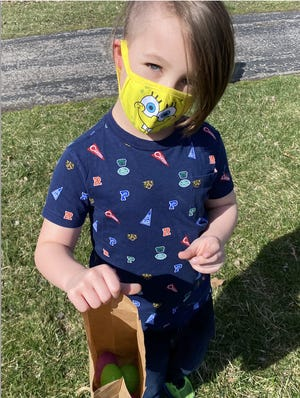 Luka Taylor, a second grader at Ritter Elementary School, smiles behind his Spongebob SquarePants mask as he shows off the five eggs he found during an Easter egg hunt hosted by the Airport High School Interact Club.