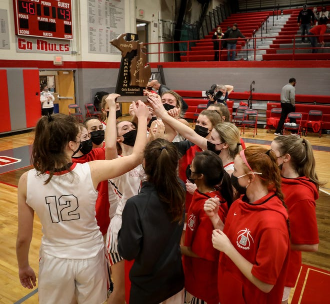 Bedford's girls basketball team celebrates with the Regional championship trophy Wednesday night.