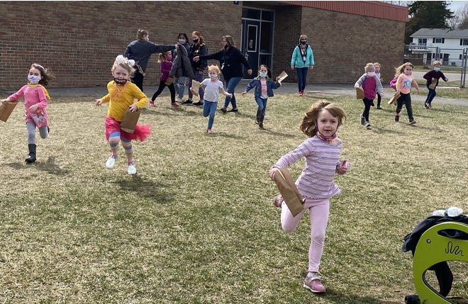 Pre-kindergarten students at Sterling Elementary School dash to the playground to search for eggs during an Easter egg hunt on Tuesday at the school.