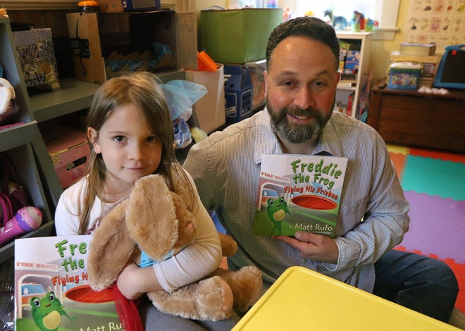 """Matt Rufo, shown at his Framingham home with his daughter Samantha, 4, wrote a children's book, """"Freddie the Frog Flying His Frisbee,"""" and has another one coming."""