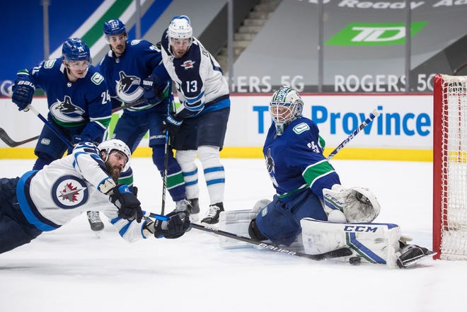 Thatcher Demko (35) stops Winnipeg Jets' Mathieu Perreault, front left, during the first period March 24 March 24, 2021, in Vancouver, British Columbia.