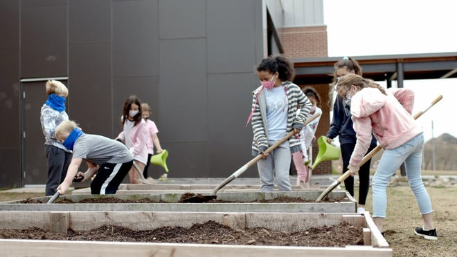 Van Buren students wearing masks and gardening at their school. Van Buren will extend their mask police following the end of the statewide mask mandate.