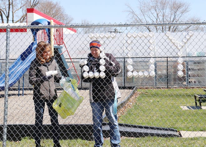 """Mary Ellen McCorvie, left, and Anne Corrigan place styrofoam cups in a fence on Chicago Street across from St. Mary's Church. The ladies, on the suggestion of Father Adam Cesarek, placed cups into the fence to spell """"Joy"""" many times as a message for Easter, which is Sunday."""