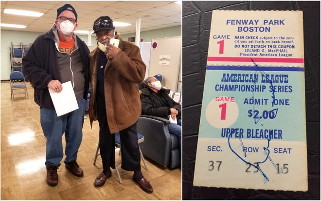 Michael Doyle, left, of Ogunquit, Maine, poses with Boston Red Sox pitcher Luis Tiant of Wells, Maine, after the two men crossed paths at York Hospital's COVID-19 Vaccine Clinic at St. Christopher's Church in York, Maine, on Feb. 9, 2021. Tiant autographed Doyle's ticket to an American League Series game at Fenway Park on Oct. 4, 1975, which Doyle had kept on hand hoping the two would cross paths.