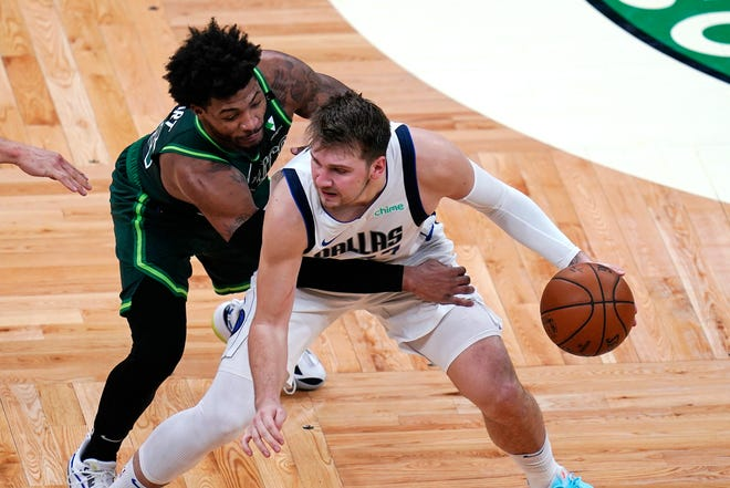 Celtics guard Marcus Smart attempts to defend the Mavericks' Luka Doncic, but Dallas' superstar torched Boston for 36 points Wednesday night at TD Garden.