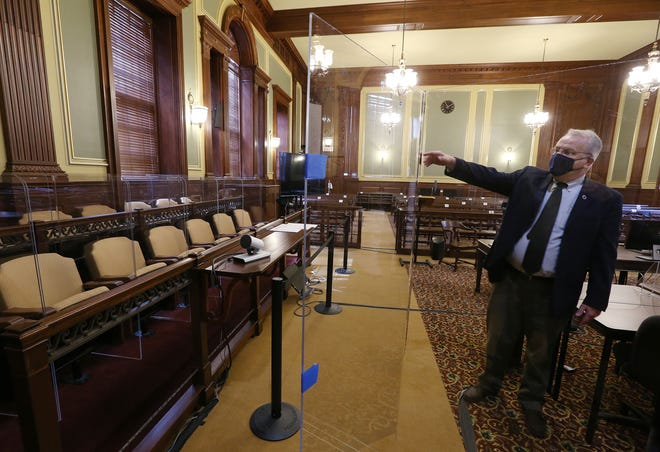 Craig Berke, assistant state court administrator, points out the clear plexiglass screens installed in Courtroom 10  at the Licht Judicial Complex that will provide safe distances and barriers between jurors, lawyers and court personnel as jury trials will begin again on Monday.