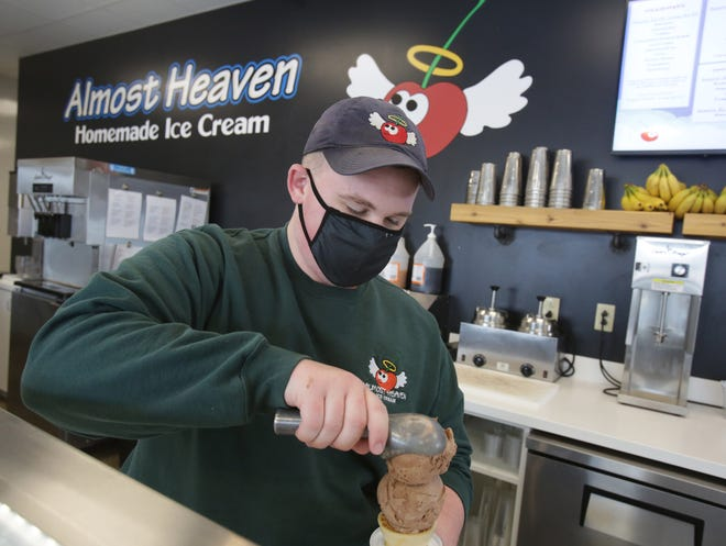 Ben Geitgey prepares a double scoop chocolate pecan at Almost Famous Homemade Ice Cream in Allliance.
