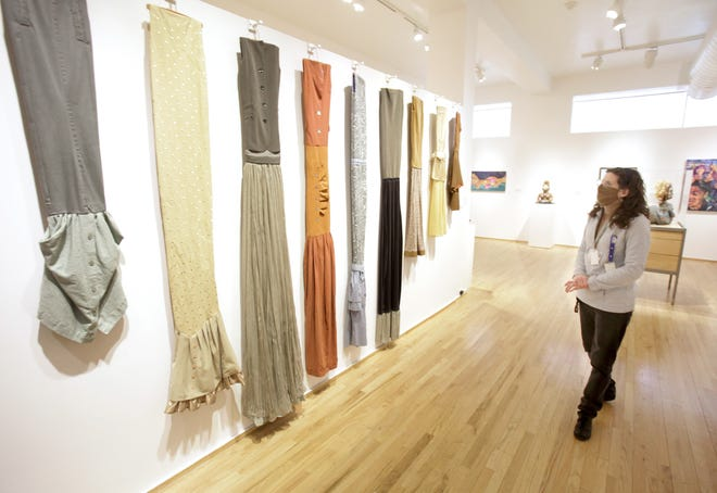 """Michelle Persons, a registrar at the Massillon Museum, talks Thursday about the artwork of Priscilla Roggencamp, part of a """"Women of Resilience"""" exhibition. The display is available free to museum visitors through May. 23."""