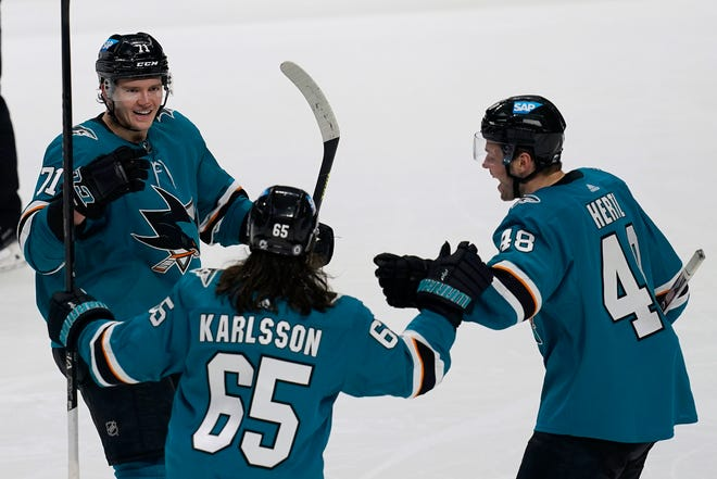 San Jose Sharks defenseman Nikolai Knyzhov, left, is congratulated by defenseman Erik Karlsson (65) and center Tomas Hertl (48) after scoring against the Minnesota Wild during the third period Wednesday. (AP Photo/Jeff Chiu)