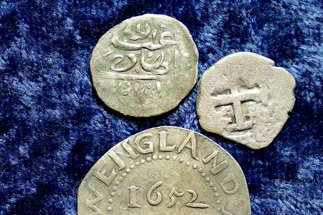 A 17th century Arabian silver coin, top, that research shows was struck in 1693 in Yemen, rests near an Oak Tree Shilling minted in 1652 by the Massachusetts Bay Colony, below, and a Spanish half real coin from 1727, right, on a table, in Warwick, R.I., Thursday, March 11, 2021. The Arabian coin was found at a farm, in Middletown, R.I., in 2014 by metal detectorist Jim Bailey, who contends it was plundered in 1695 by English pirate Henry Every from Muslim pilgrims sailing home to India after a pilgrimage to Mecca. (AP Photo/Steven Senne)