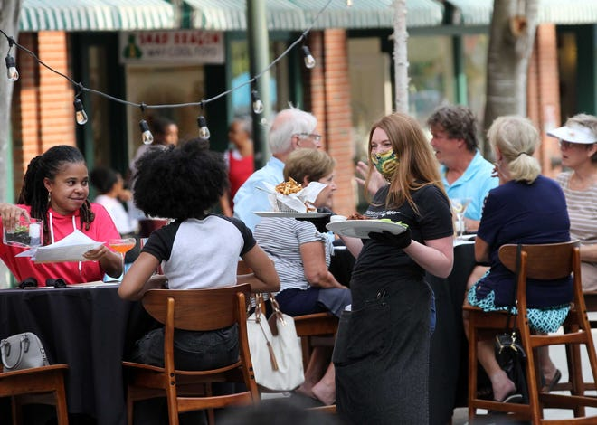 Restaurants serve patrons and diners at designated outdoor cafe areas in historic downtown New Bern. With the easing of North Carolina's COVID-19 alcohol and occupancy restrictions, area restaurants and bars are reporting an increase in business and, hopefully, a pathway to normalcy. [Gray Whitley / Sun Journal Staff]