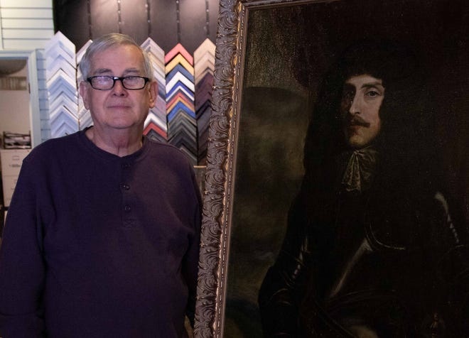 Ed Macomber stands beside the Earl of Craven portrait he has finished restoring.