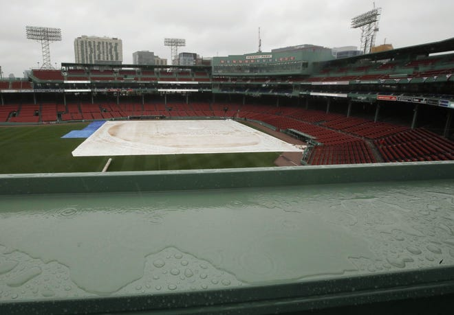 A tarp covers the infield and a puddle accumulates on the Green Monster ledge during steady rain at Fenway Park.