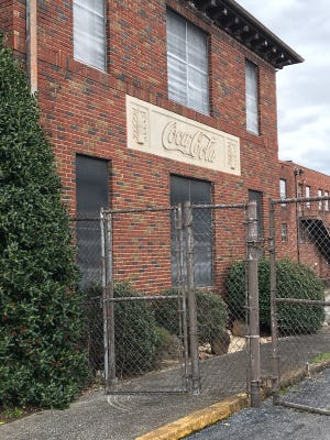 Gates and doors at what was once a Coca Cola bottling facility on Walnut Street have been closed for years. The building will be demolished this month.