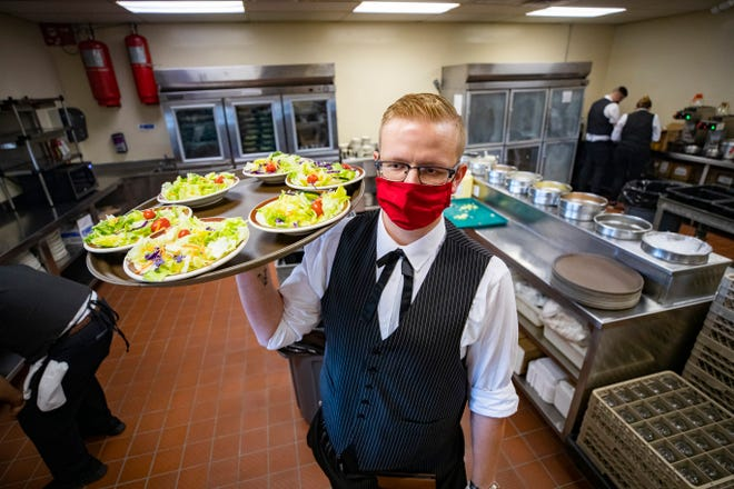 Adam Detunno gets salads ready for customers at Angelo's Steak Pit on Thursday, April 1, 2021. Detunno works as a server at Angelo's.