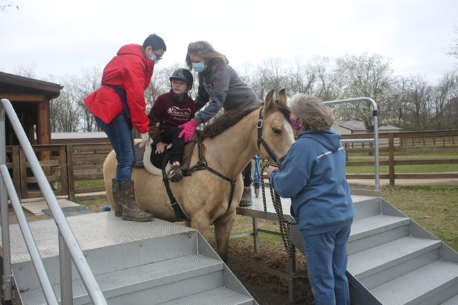 Volunteers at Manes & Miracles help a patient onto the horse to start the equine part of therapy.