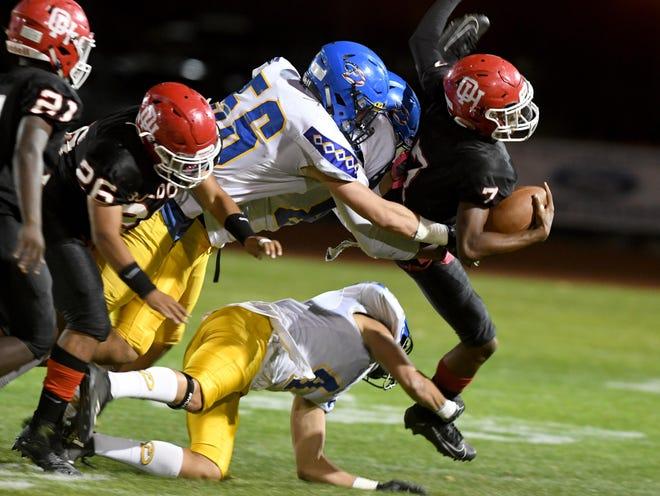 Oak Hills' Latavion Lispcomb tackled by Serrano defenders during a game at Oak Hills High School last season.