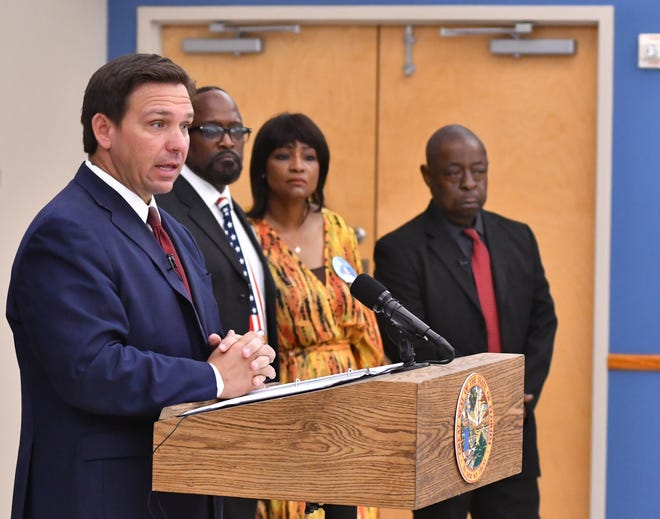 Gov. Ron DeSantis, left, stands with Bobby and Kiyan Michael and Jamiel Shaw Sr., whose sons were killed by people who entered the country illegally, one in a shooting and one in a traffic accident. They were at a news conference at the American Police Hall of Fame & Museum in Titusville.