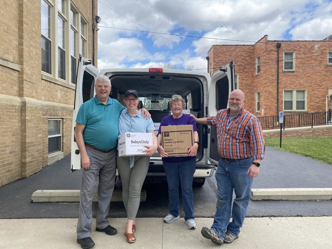 (L-R) Volunteers Jim Anderson, Audrey Glass, Lynn Anderson, and Joe Holbrook from Bottoms Up, pose with diapers and wipes they collected outside of St Peter's Catholic Church in Chillicothe.