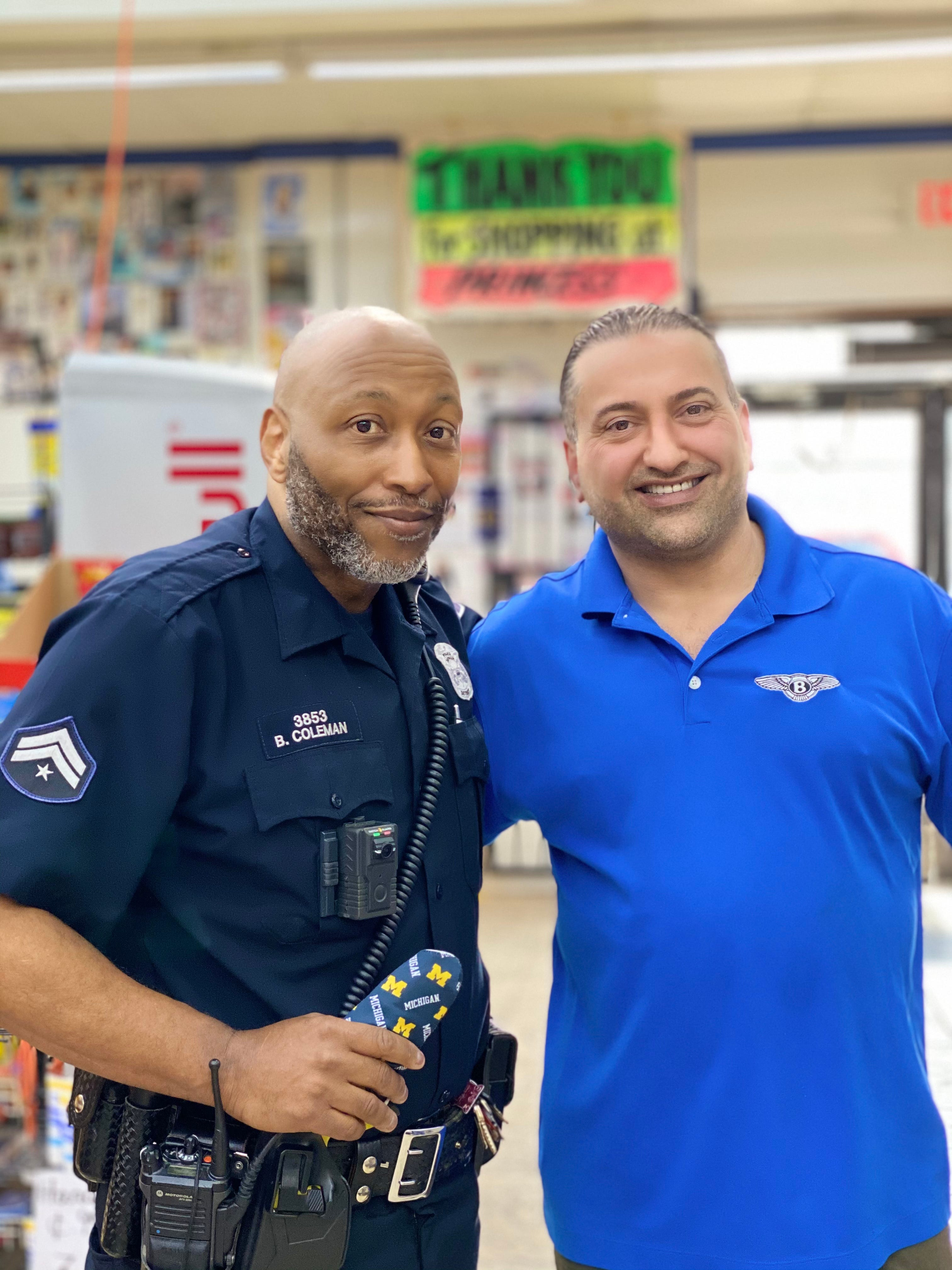 Officer Barren Coleman standing with Sal Sybri, 43, the owner of Princess Superette Market, a liquor store apart of the neighborhood Coleman patrols.