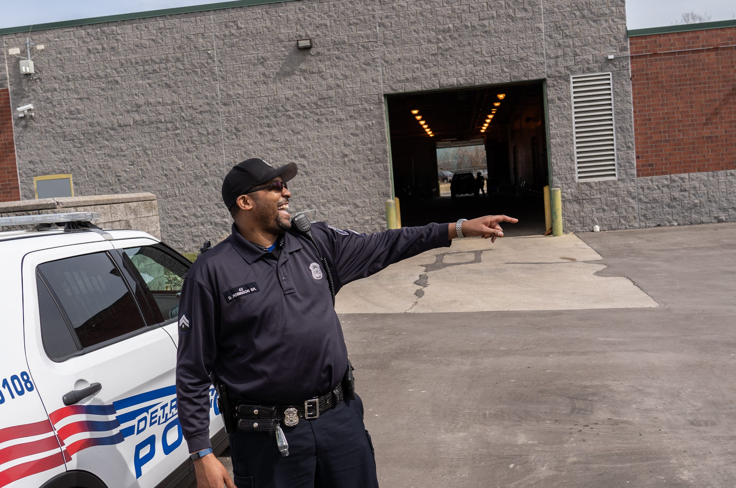Detroit Police Department Neighborhood Police Officer Dan Robinson laughs with another officer after handing out gun safety information and gun locks door-to-door along Fenelon Street on Detroit's east side on Thursday, March 25, 2021.