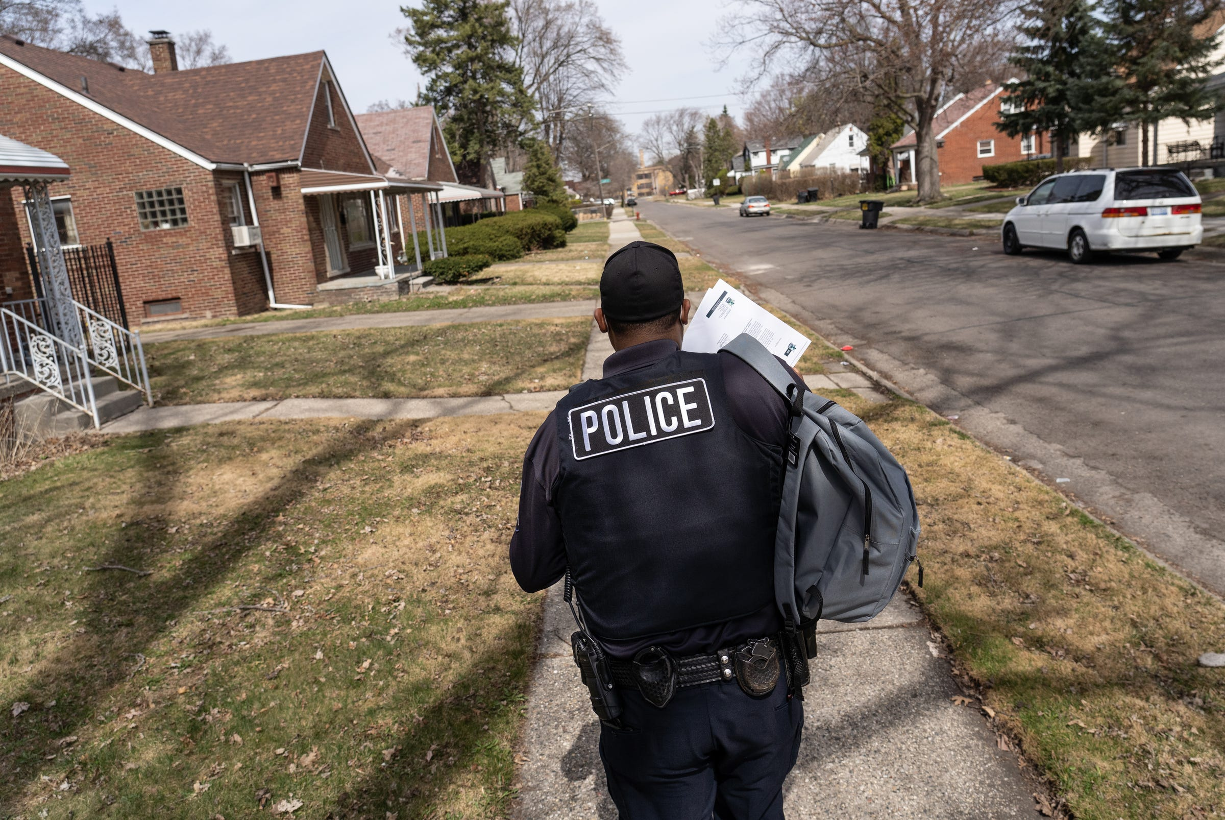Detroit Police Department Neighborhood Police Officer Dan Robinson walks around while handing out gun safety information and gun locks as officers go door-to-door along Fenelon Street on Detroit's east side on Thursday, March 25, 2021.