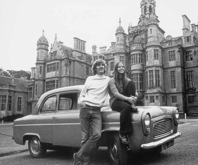 Students Steve Ainlay and Judy (Gardner) Cherry pose with a car on the front circle of Harlaxton Manor.
