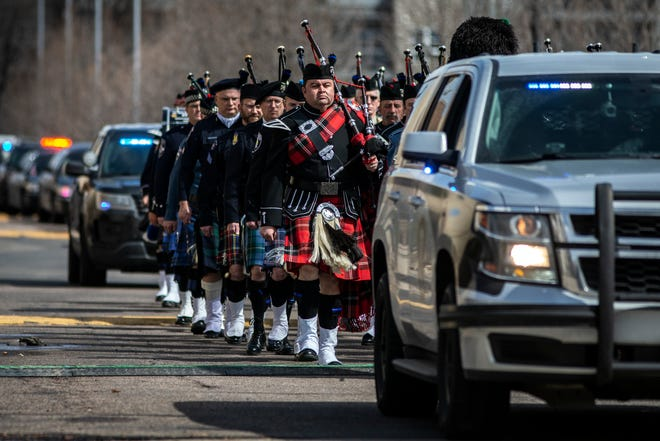A parade of bagpipers in honor of slain Boulder Police Officer Eric Talley march out of a memorial service at Flatirons Community Church on March 30, 2021 in Lafayette, Colorado. Officer Talley was one of ten people killed in a shooting at a King Soopers grocery store on March 22 in Boulder, Colorado.