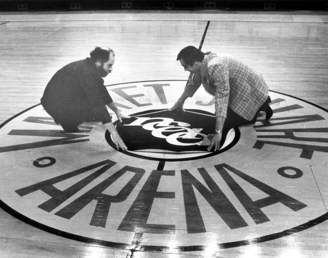 On March 20, 1980, Larry Taylor (left) and Ed Grover of the Market Square Arena staff put the NCAA logo on the basketball court in preparation for the 1980 Final Four. Purdue, Iowa, UCLA and eventual champions Louisville battled for the title.