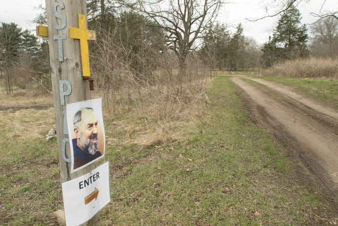 Pictures of St. Padre Pio, shown Thursday, April 1, 2021, mark the entrance to property on Chilson Road in Genoa Township earmarked for development into a prayer campus with a chapel, outdoor grotto and symbolic statues.