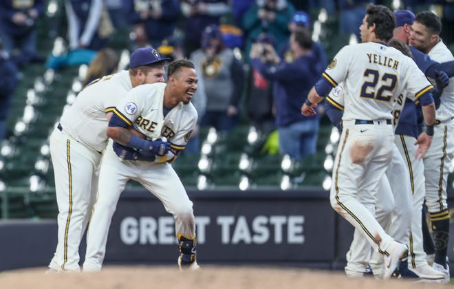 Brewers players celebrate with Orlando Arcia after Arcia's run-scoring fielder's choice wins the opener for the Brewers in the bottom of the 10th inning.