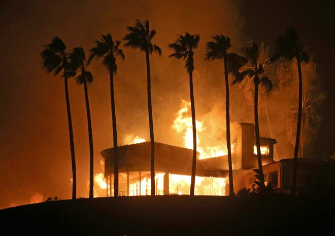 FILE - In this Nov. 9, 2018, file photo, palm trees frame a home being destroyed by the Woolsey wildfire above Pacific Coast Highway in Malibu, Calif. Southern California Edison will remove 11,000 palm trees in its service territory that are too close to power lines and pose a fire risk. Palms are not only a hazard when they are close to lines but fronds can be carried long distances by the wind and hit electrical wires, the utility said in a recent statement. (AP Photo/Reed Saxon, File)