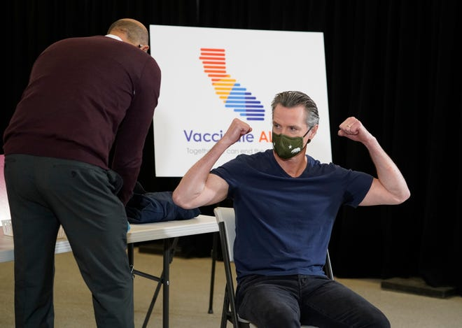California Gov. Gavin Newsom reacts after being inoculated by Dr. Mark Ghaly, California's Health and Human Services secretary, on Thursday, April 1, 2021. Newsom was vaccinated with the new one-dose COVID-19 vaccine by Johnson & Johnson.
