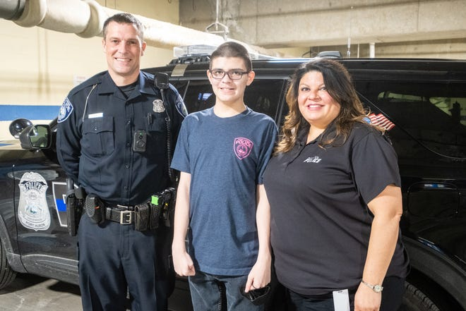 From left, Port Huron Police Community Service Officer Duane Hunger poses for a portrait with Brady Proctor, 13, and his mother Jessica Proctor, Wednesday, March 31, 2021, in the department's garage at the Municipal Office Center in Port Huron. Brady, who is autistic, was originally afraid of police officers, sirens and lights until he was able to spend more time with them.