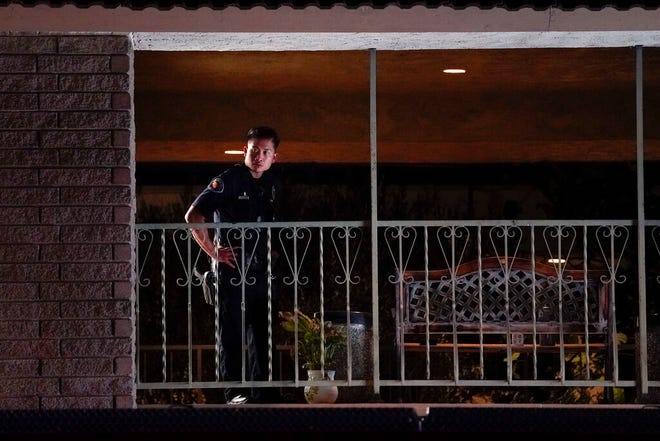A police officer surveys the scene after a shooting at an office building in Orange, Calif., Wednesday, March 31, 2021. The shooting killed several people, including a child, and injured another person before police shot and wounded the suspect, police said. (AP Photo/Jae C. Hong)