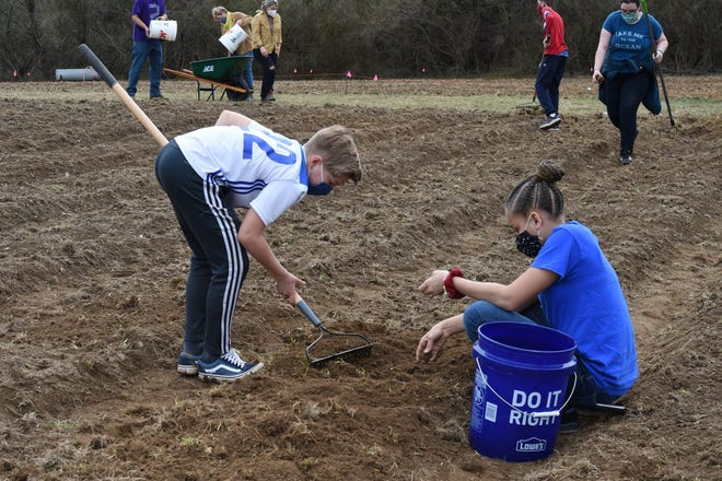 Students from Kate Collins Middle School work in a new vegetable garden at Waynesboro's Berkeley Glenn Elementary School Wednesday, March 24. The garden is a joint project between Waynesboro Public Schools and the Allegheny Mountain Institute.