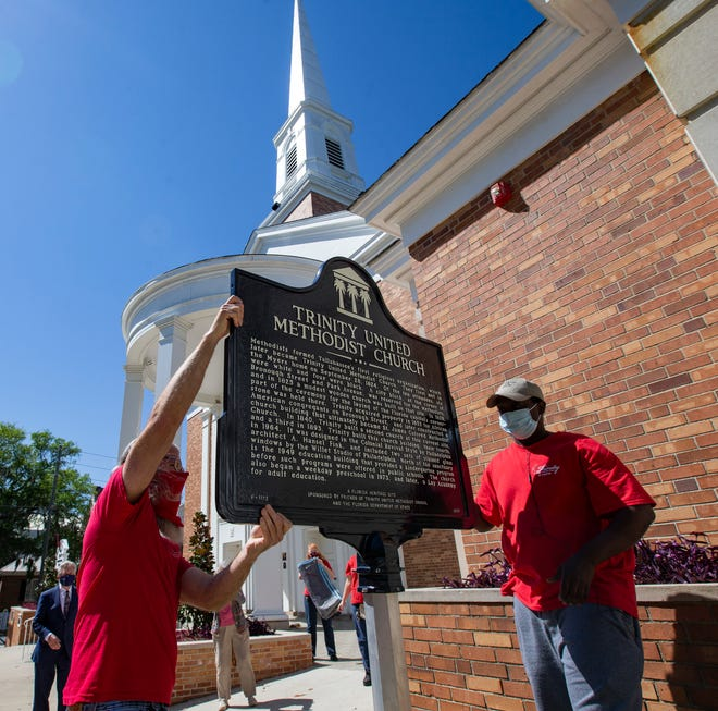 In advance of Trinity United Methodist Church's upcoming 200th anniversary, Brett Ingram, facility director at Trinity United Methodist Church, left, and Ben Armstead place a historical marker on a pole in front of the church on Thursday, April 1, 2021.