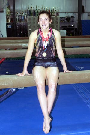 Ady Wahl sits on a balance beam with her medals during a recent practice at Zanesville Gymnastics on Richards Road. Wahl recently won the All-Around state title in Level 10 at the USA Gymnastics Ohio State Championships. She will compete in the regional in April.