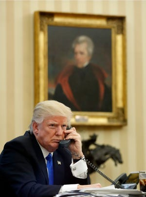 President Donald Trump speaks on the phone with Prime Minister of Australia Malcolm Turnbull in the Oval Office of the White House, Saturday, Jan. 28, 2017 in Washington. Behind Trump is a portrait of President Andrew Jackson.