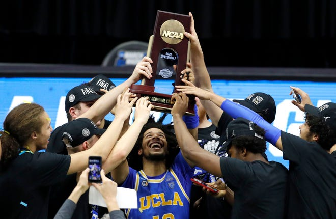 Players put hands on the trophy as UCLA Bruins guard Tyger Campbell (10) hoists in above his head after defeating Michigan during the Elite Eight round of the 2021 NCAA Tournament.