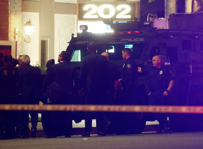 Police officers stand outside an office building where four people, including a child, were killed in a shooting on March 31, 2021 in Orange, California.