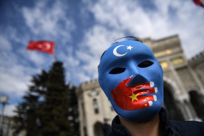 A demonstrator wearing a mask painted with the colors of the flag of East Turkestan takes part in a protest by supporters of the Uyghur minority on Thursday at Beyazid Square in Istanbul, Turkey.