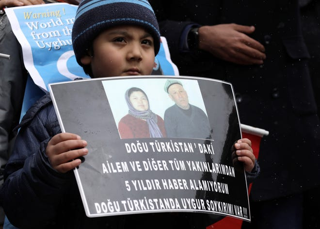 "A Uyghur boy holds a placard that reads: ""I cannot have any news from my family and relatives in Eastern Turkistan"", during a protest near the Chinese embassy in Ankara, Turkey, on March 25."