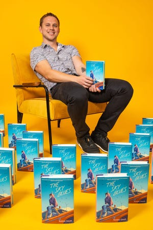 """Robbie Couch with his book, """"The Sky Blues,"""" out April 6."""
