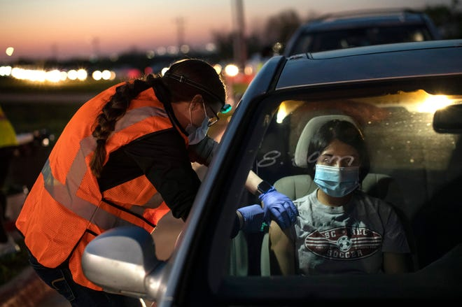Volunteer Samantha Bennett, a nursing student at ACC, gives Jocelyn Sanchez, 19, her first dose of the Pfizer vaccine against the coronavirus at a drive-thru vaccination center at the stadium for Manor High School on Thursday.