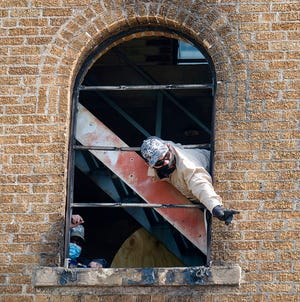 Workers board up windows in the Buford Tower downtown. A fire that started at a nearby homeless camp spread to the histoirc tower Thursday night, April 1, 2021.