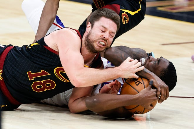 Cleveland Cavaliers' Matt Dellavedova, left, ties up Philadelphia 76ers' Shake Milton for a jump ball during the second half of an NBA basketball game Thursday, April 1, 2021, in Cleveland. [Ron Schwane/Associated Press]