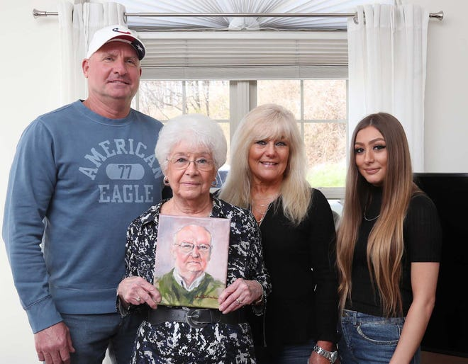 Shirley Arnold shows the painting of her late husband, Harold Arnold, as she stands with stepson Bradley Arnold, from left, daughter Victoria Nacci and granddaughter Lexi Nacci in her North Canton home Friday.