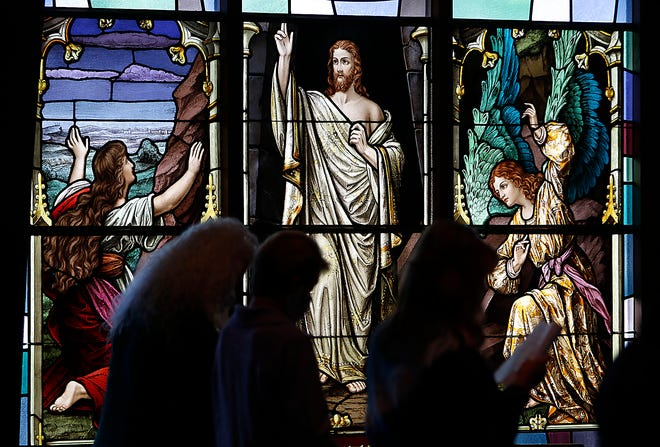 The Resurrection stained glass window is seen as worshipers stand as they sing Beneath the Cross of Jesus during the Ashland County Ministerial Association's annual Community Good Friday service on Friday, April 2, 2021 at Trinity Lutheran Church. TOM E. PUSKAR/TIMES-GAZETTE.COM