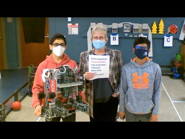 Dillon Mehta and Adit Paul pose with Central Middle School teacher Lolly Williams with their robotics project.